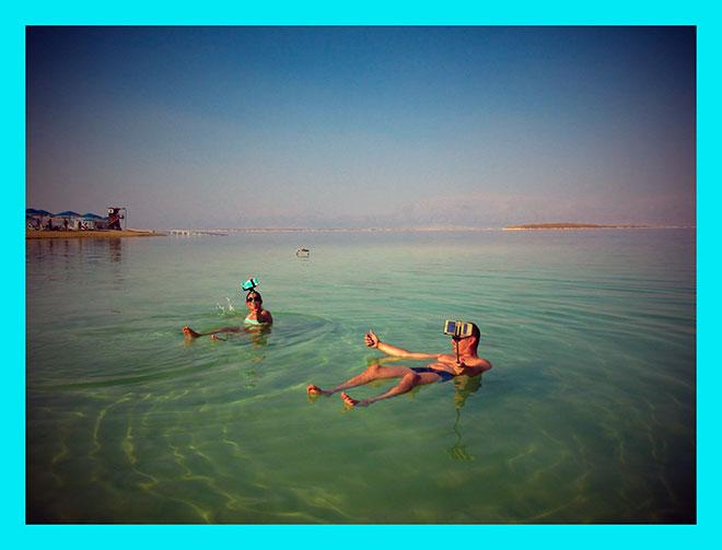мужчина и женщина делают селфи в мертвом море в Израиле