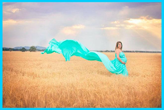 беременная девушка в красивом бирюзовом платье идет по полю