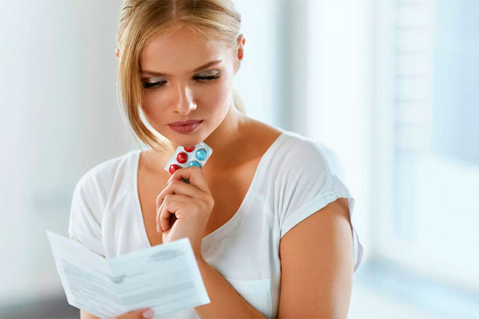 девушка читает инструкцию от таблеток