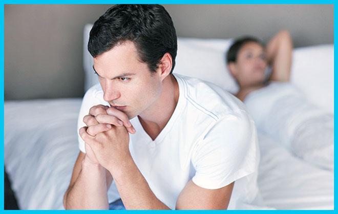 грустный мужчина сидит на кровати