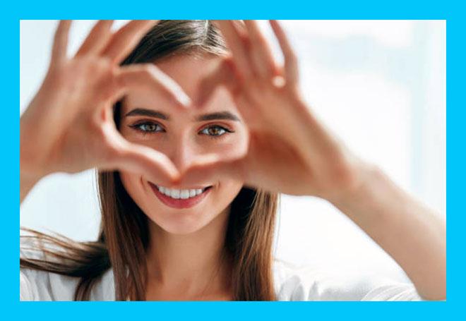 счастливая девушка показывает сердце руками