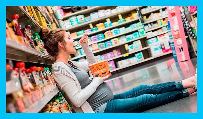 беременная женщина сидит на полу в магазине и ест мороженное